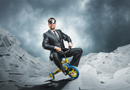 Odd businessman riding a small bicycle against paper background