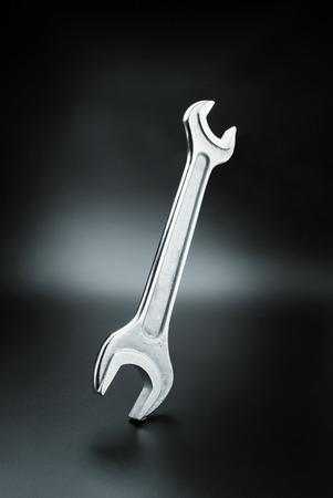 Stainless steel wrench on dark background