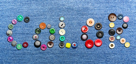needlecraft product: Colorful buttons on blue background forming the word color