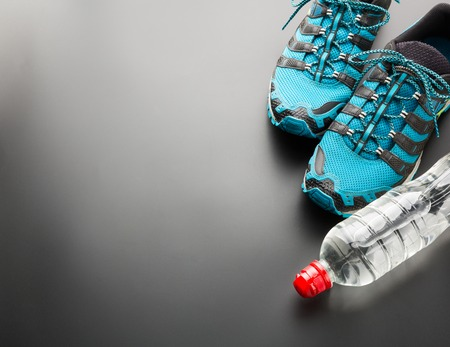 running shoes: Runners and a bottle of water on grey background Stock Photo