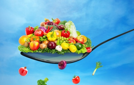 vegetable cook: Spoon full of various fruit and vegetables on blue sky background