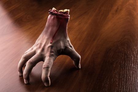 流血カットの腕が木製のテーブルの上に立つ