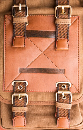 buckled: A closeup of brown leather bag buckle