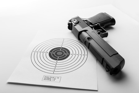 individual sport: Paper target and pistol on white background Stock Photo
