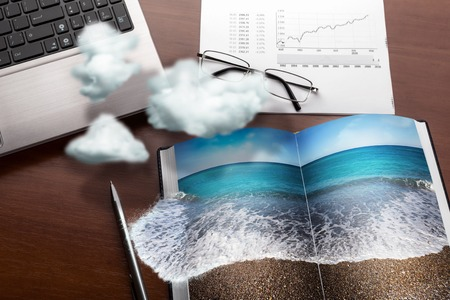 dream planning: Office table in clouds with the sea on the notebook. Vacation concept