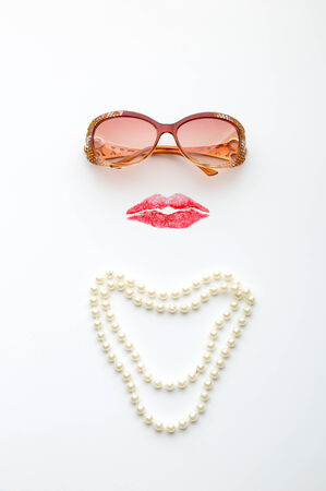 Glasses, lips and necklace forming woman face on white background photo