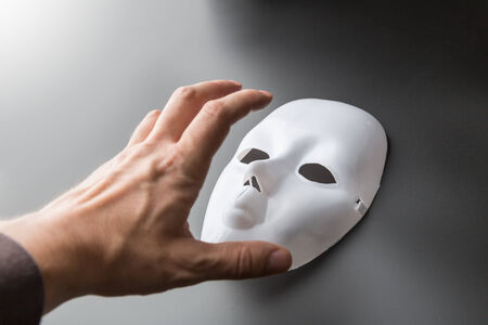 showpiece: Human hand tries to take theater mask on grey background