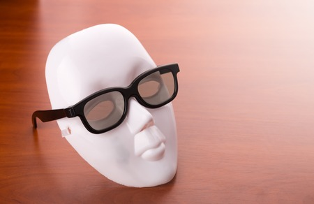 showpiece: Theater mask in glasses on the wooden table Stock Photo
