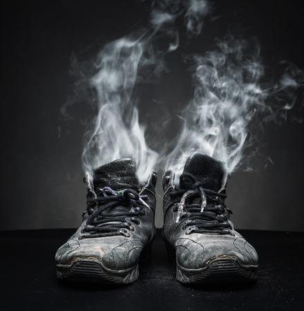 proceeds: Viejos zapatos de trabajo negro del cual los ingresos de humo Foto de archivo