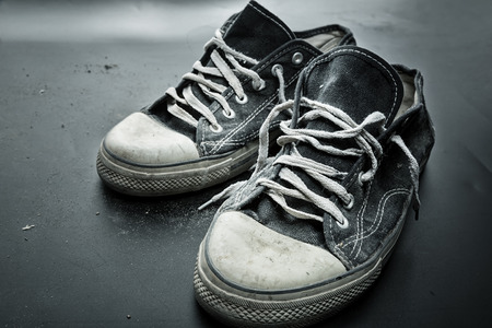 shoelace: Old sports trainers on the grey floor Stock Photo