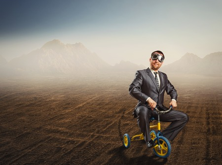 Odd businessman riding a small bicycle against desert background