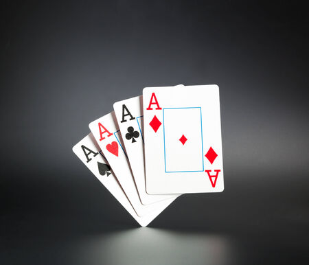 Four aces standing on dark background photo