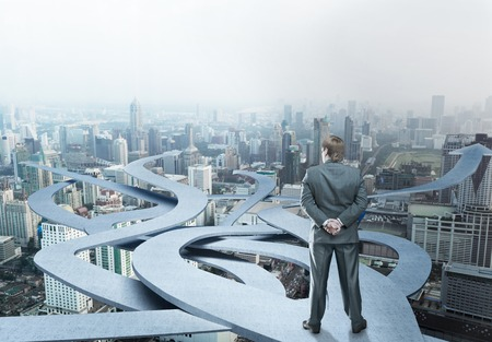 Businessman stands choosing his way on city background