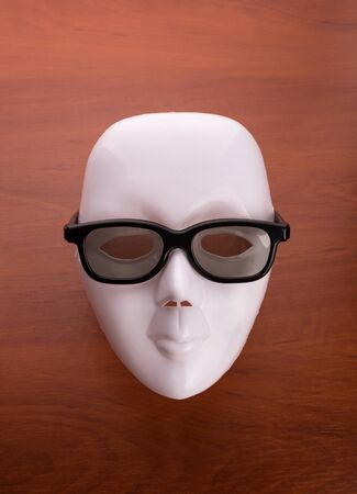 showpiece: Theater mask in business glasses on the wooden table