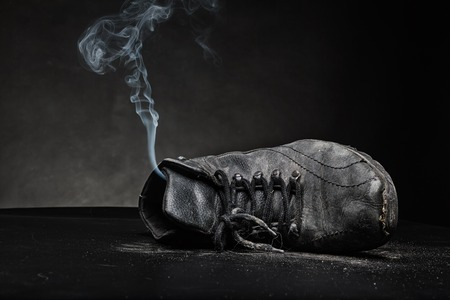 Old black work shoe from which the smoke proceeds photo