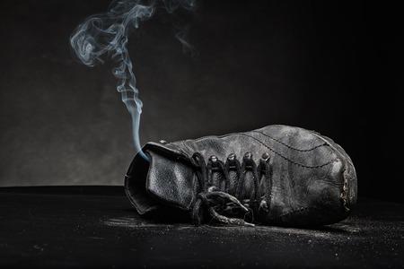 pieds sales: Vieille chaussure de travail au noir � partir de laquelle la fum�e produit