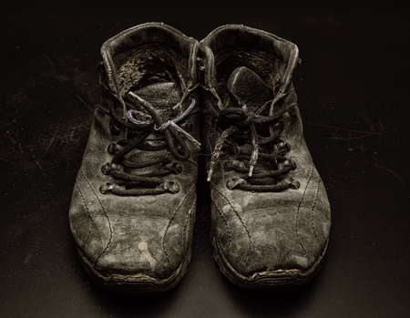 Old worn out shoes on the black floor photo