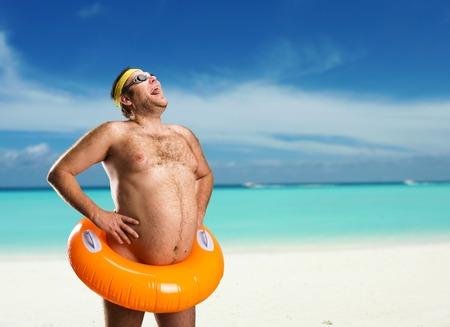 Etrange homme nu avec enfants bouée sur la plage
