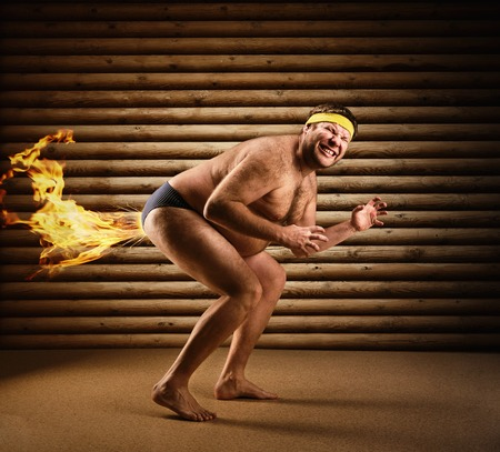 Very strange man farts by fire on the background of wooden wall