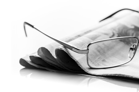 lieing: A closeup of glasses lieing on the heap of newspaper
