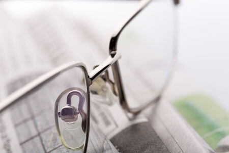 lieing: A closeup of glasses lieing on the newspaper