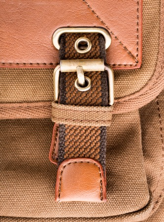 buckled: A closeup of vintage brown backpack buckle