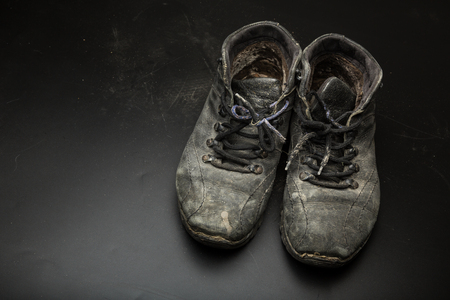 Oude versleten schoenen op de vloer Stockfoto