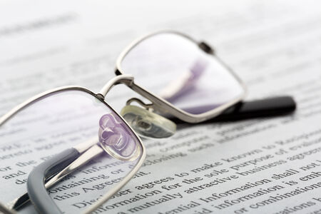 A closeup of glasses lieing on the newspaper