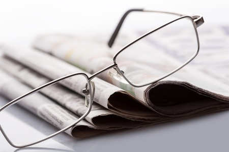 lieing: Closeup of glasses lieing on the newspapers