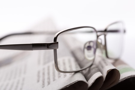 lieing: Macro of glasses lieing on the heap of newspaper Stock Photo