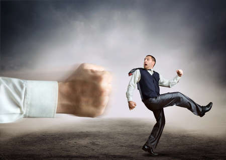 preasure: Businessman runs from a big fist on grey background Stock Photo