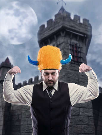 odd: Odd businessman in party helmet showing his strenth agaist ancient tower