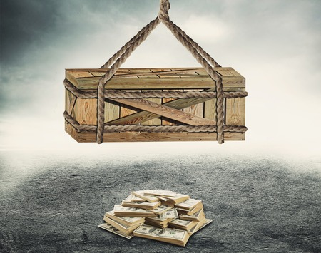 full suspended: Big wooden box suspended above a pile of money over grey background Stock Photo