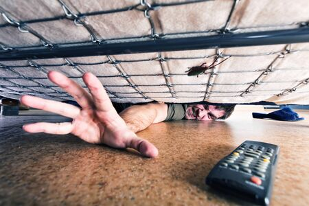 under control: Man trying to get something under the couch