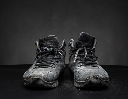 out of work: Old black worn out work shoes on the floor