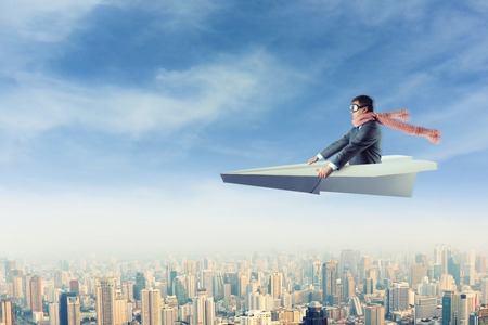 Businessman with the scarf on paper airplane above the city