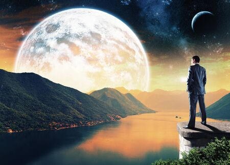 landing light: Businessman standing on the edge in the night and looking at the big moon Stock Photo