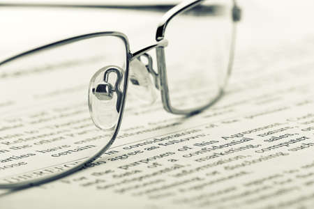 lieing: Closeup of glasses lieing on the newspaper. Toned