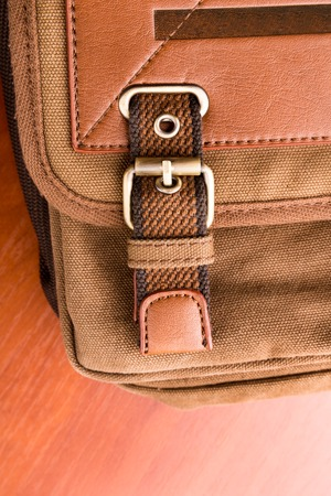 buckled: Closeup of brown backpack buckle on wood Stock Photo