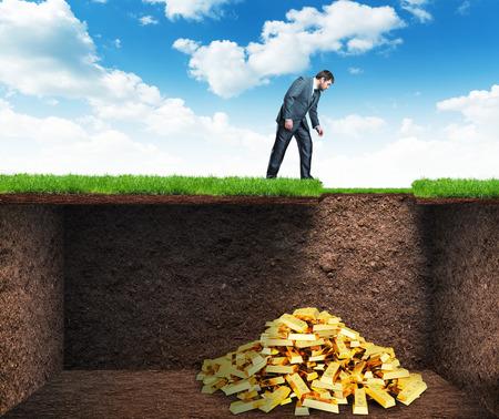 jaskinia: Biznesmen pochyla się i patrzy na skarb w ziemi
