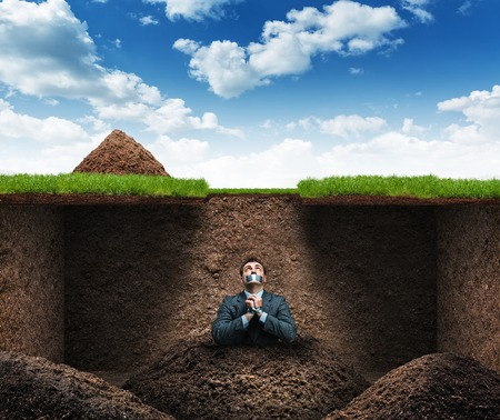 Businessman sits as hostage underground in the soil