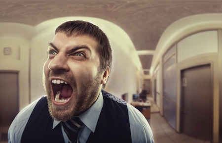 man screaming: Crazy businessman shouting at office