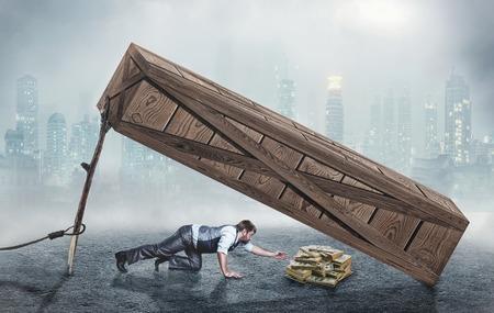 Businessman trying to get money under big wooden box trap Standard-Bild