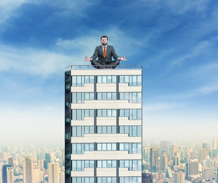view of an elegant office: Businessman sits meditating on the top of a high building against city