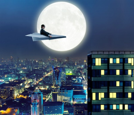 paper airplane: Businessman on paper airplane is flying above the city in the night