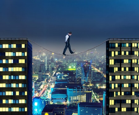 tightrope: Businessman thinking going the tightrope between two buildings at night