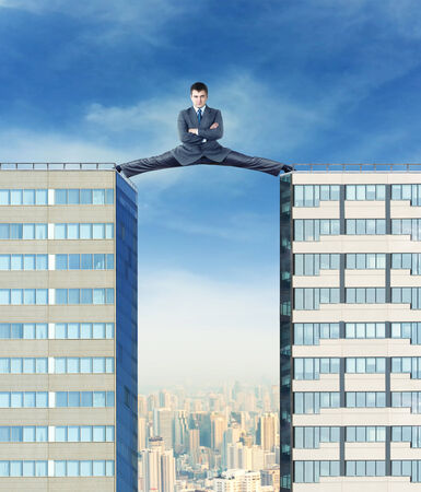 splits: Businessman sits in the splits between two high buildings against the city
