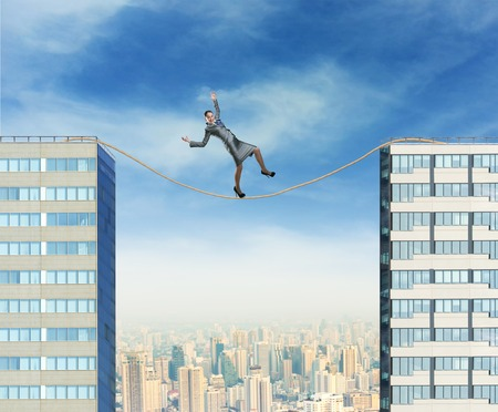 Businesswoman balancing on the rope between two high builgings against the city photo