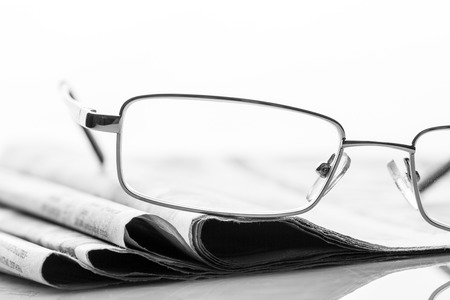 lieing: Closeup of glasses lieing on the heap of newspaper