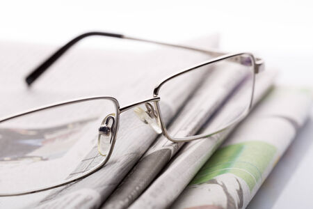 lieing: Macro of glasses lieing on the newspapers